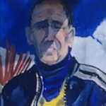 Portrait of man by his blue motorbike with blue leather jacket